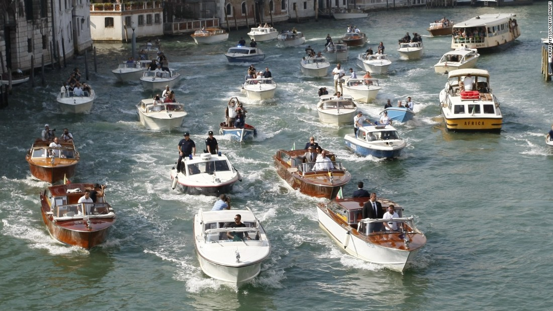 Boats surround the taxi boat of George Clooney and his wife, Amal Alamuddin Clooney, in September 2014 on the Grand Canal in Venice.