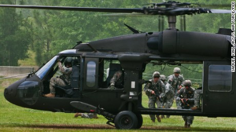 Rangers make their way to the UH-60 Blackhawk to exit the area during a scenario at the 6th Ranger Training Battalion's annual open house event, May 12 at Eglin Air Force Base, Fla. The event was a chance for the public to learn how Rangers train and operate. The event displays showed dive equipment, weapons, a reptile zoo and zodiac boats among others. The demonstrations showed off hand-to-hand combat, a parachute jump, a down-pilot scenario and others. (U.S. Air Force photo/Samuel King Jr.)