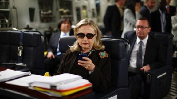 "Hillary Clinton, while U.S. secretary of state, checks her Blackberry on a military plane in October 2011. Clinton said she used a private email account for her official work at the State Department and that she did so out of convenience. But she admitted in retrospect ""it would have been better"" to use multiple emails."