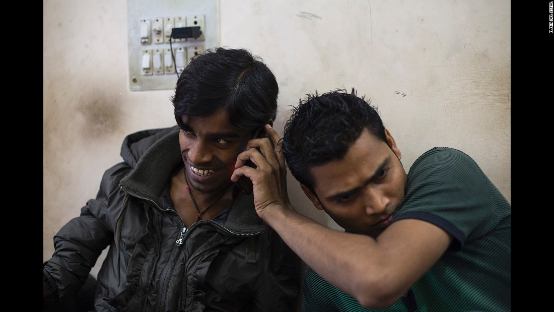A friend holds a cell phone to Kumar's ear as he talks to his mother in November.