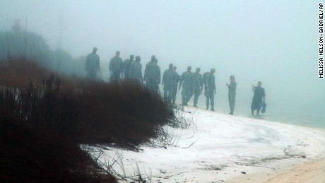 Military personnel wade in the water and search on the beach under heavy fog at Eglin Air Force Base, Fla., Wednesday, March 11, 2015, for the wreckage of a military helicopter that crashed with 11 service members aboard. The helicopter went down Tuesday evening. A Pentagon official says all aboard are presumed dead. (AP Photo/Melissa Nelson-Gabriel)