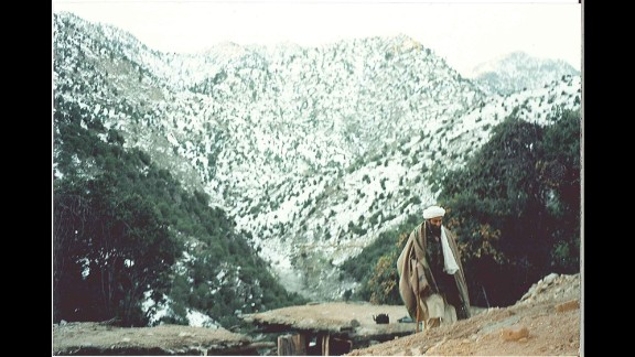 Bin Laden hikes alone at the base of a mountain. As U.S. troops closed in on Tora Bora in late 2001, bin Laden escaped.  A decade later, U.S. Navy SEALs killed him at his next hideout in Abbottabad, Pakistan.