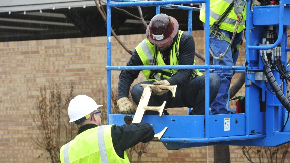 Facility workers remove the letters from the SAE house on Monday, March 9.