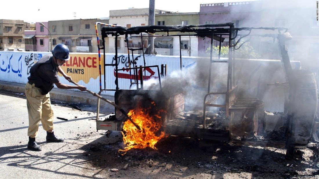 A policeman extinguishes a burning auto-rickshaw torched by an angry mob following the raid.