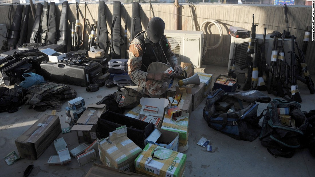 A Pakistani paramilitary soldier inspects weapons recovered after Rangers raided Muttahida Qaumi Movement (MQM) offices in Karachi.