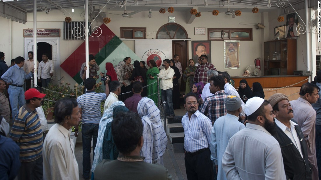 Pakistani supporters of MQM political party gather outside party  headquarters following a raid by paramilitary Rangers in Karachi.