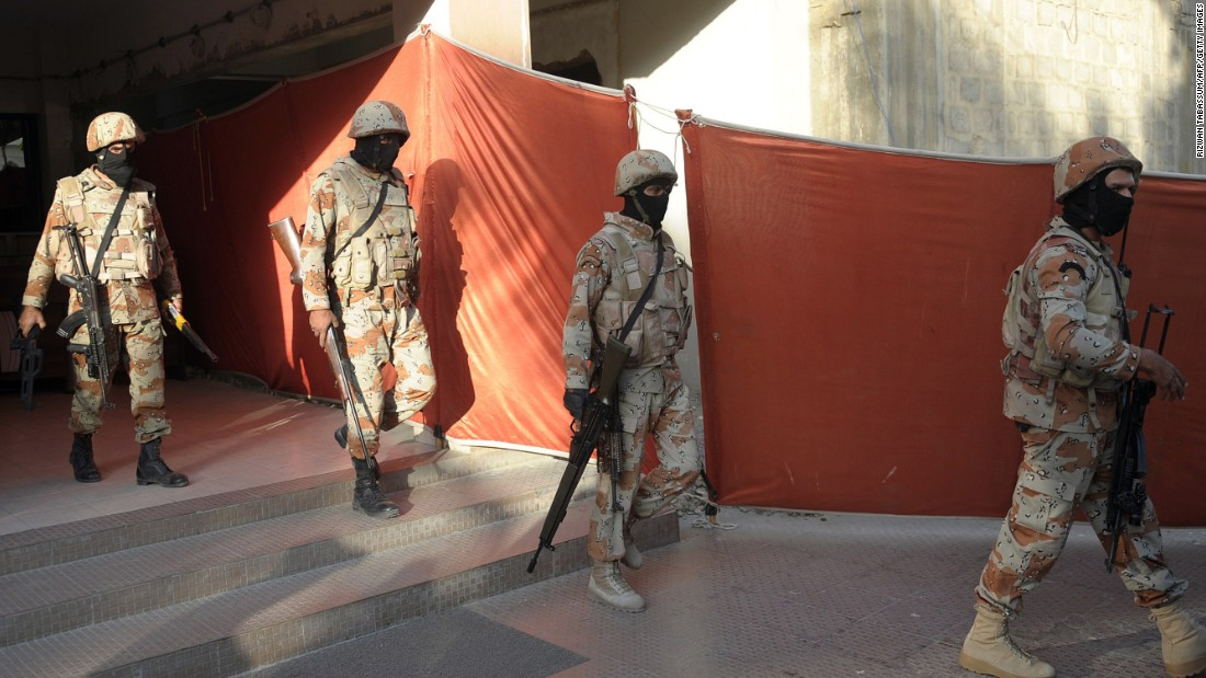 Pakistani paramilitary soldiers leave the headquarters of the MQM political party after a raid in Karachi.