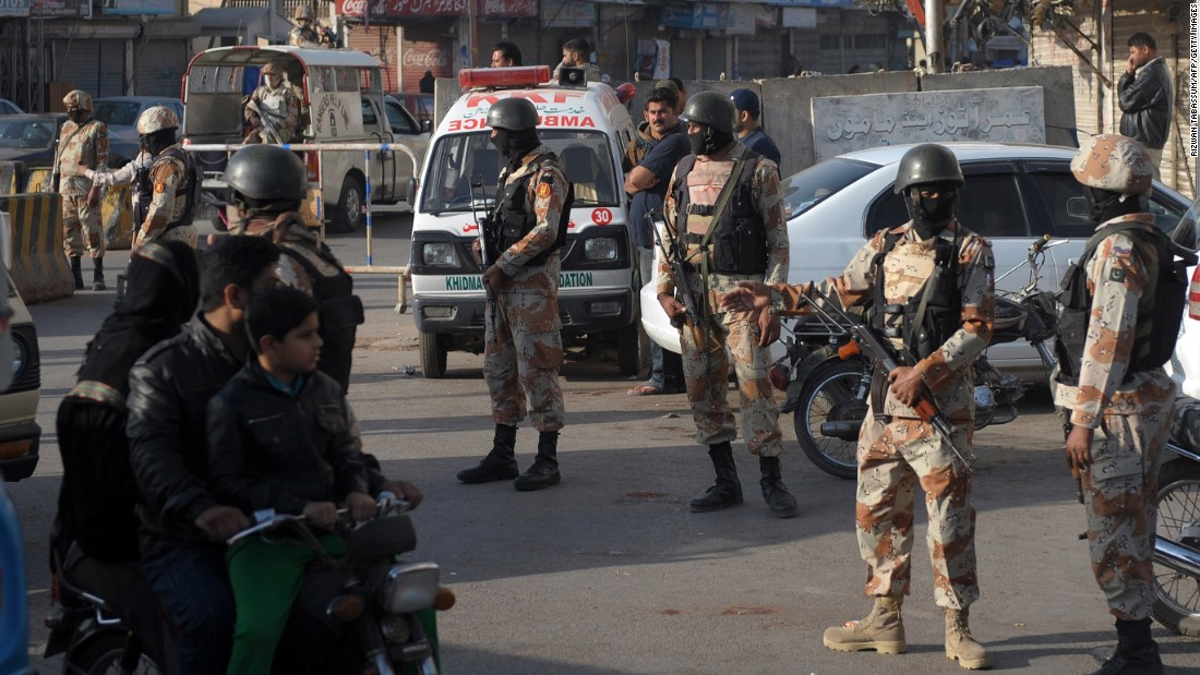 Pakistani paramilitary soldiers cordon off a street during a raid on the offices of MQM political party in Karachi.