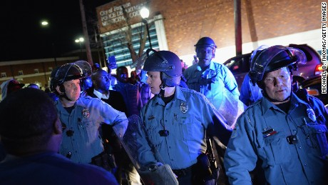 Police in riot gear respond to demonstrators blocking traffic in Ferguson late Wednesday, March 11.