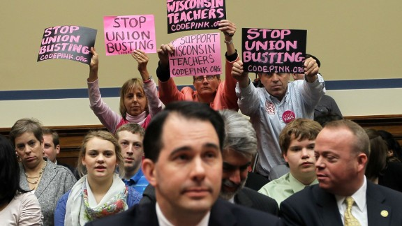 Members of Code Pink (left to right) Medea Benjamin, Liz Hourican and Tighe Barry, hold signs to protest as Walker (center) takes his seat during a hearing before the House Oversight and Government Reform Committee April 14, 2011, on Capitol Hill in Washington, D.C.