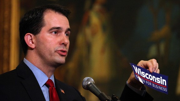 Walker holds up a 'Wisconsin is open for business' bumper sticker as he speaks during a ceremonial bill signing outside his office at the Wisconsin State Capitol on March 11, 2011, in Madison, Wisconsin.