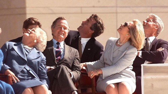 Former President George H.W. Bush (second left), his wife Barbara Bush (left), their son Jeb Bush (center), then-first lady Hillary Clinton (second right), and former then-President Bill Clinton (right) look up to see the U.S. Army Golden Knights parachute team November 6, 1997 at the conclusion of the dedication ceremony of the George Bush Library in College Station, Texas.