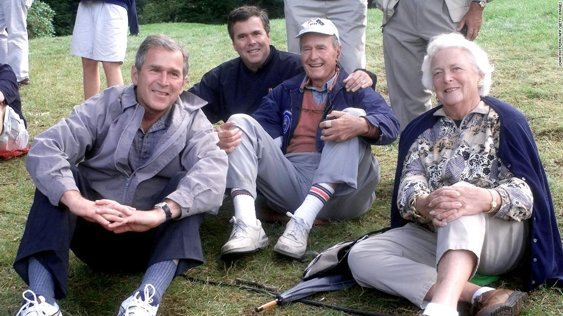 The Bush family, (left to right) former U.S. President George W., former Florida Governor Jeb, former President George H.W. and his wife Barbara, watch play during the Foursomes matches September 25, 1999 at The Country Club in Brookline, Massachusetts the site of the 33rd Ryder Cup Matches.