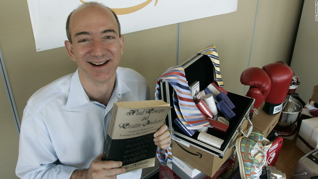 "Amazon.com debuted in 1995 and helped turn the Internet into the commercial powerhouse that it is, paving the way for a bevy of services promising easy ordering, quick delivery and cheap prices. Amazon founder and CEO Jeff Bezos is pictured in 2005 with a copy of ""Fluid Concepts and Creative Analogies"" by Douglas Hofstadter, the first book sold online by Amazon."