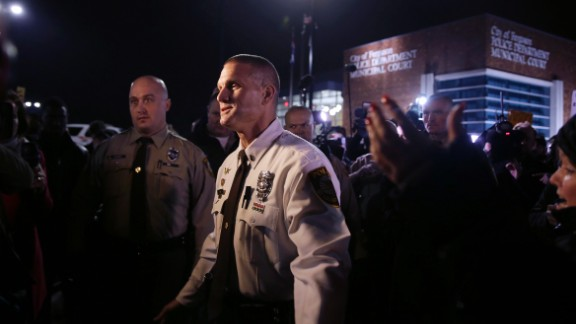 St. Louis County police Lt. Jerry Lohr walks through a crowd of protesters in Ferguson on March 12, trying to get them to move out of t