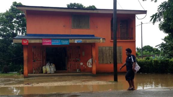 A person walks past flooding near Port Vila on March 13.