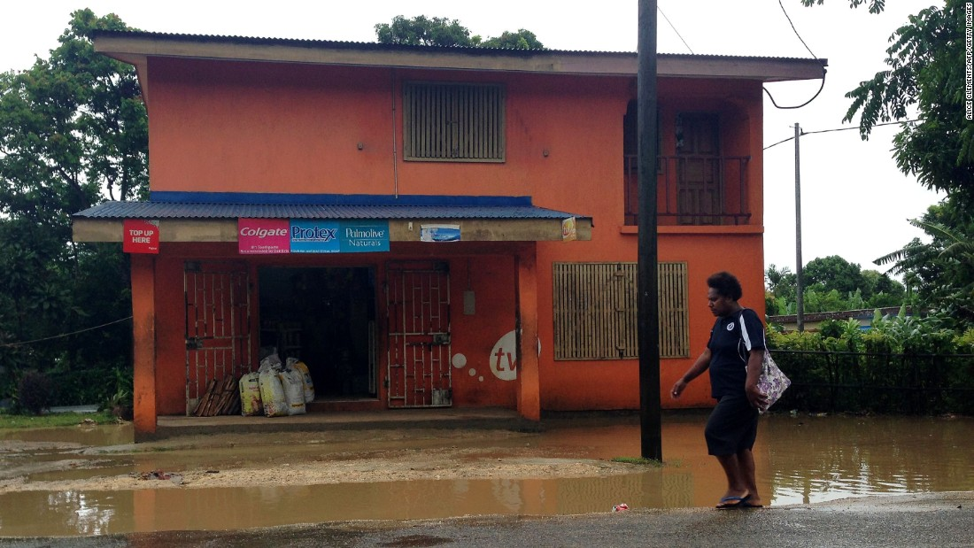 A person walks past flooding near Port Vila on March 13.