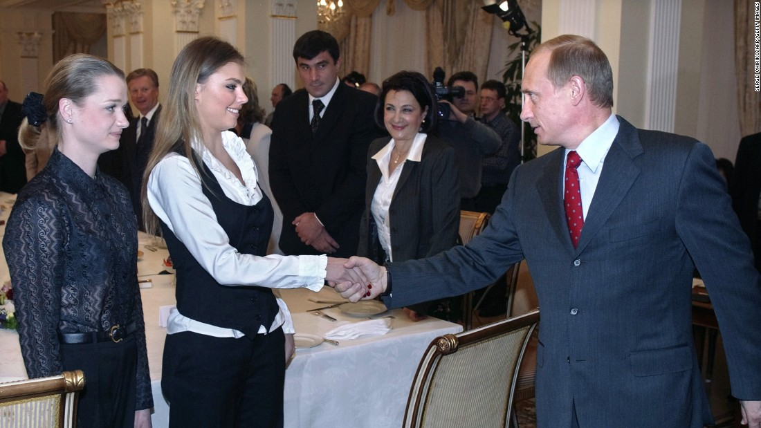 Putin shakes hands with famous Russian gymnasts Alina Kabayeva, center, and Svetlana Khorkina in March 2004.