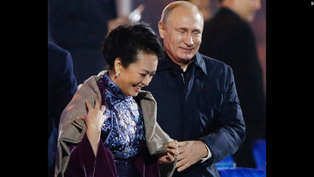Putin puts a shawl on Peng Liyuan, wife of Chinese President Xi Jinping, as they arrive to watch a fireworks show in Beijing in November.