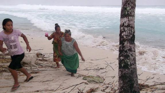 People move away from the beach March 13 on the island of Kiribati.