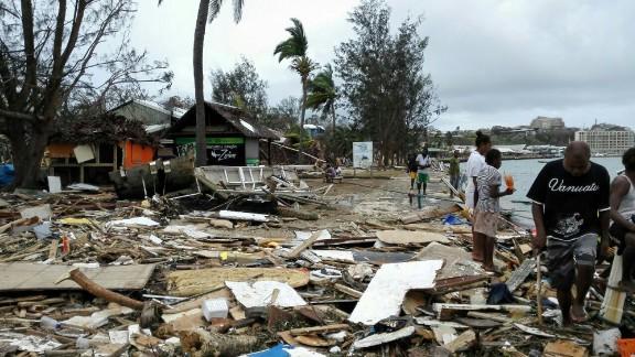 Locals walk past debris in Port Vila on March 15.