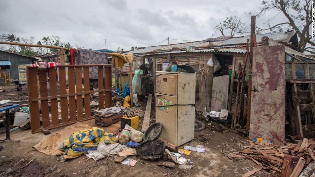 A resident stands in her badly damaged home outside Port Vila on March 15.