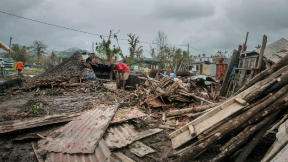 Residents work amid the debris left by the cyclone outside Port Vila on March 15.
