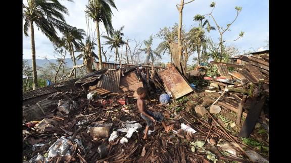 A boy kicks a ball through the ruins of his family home as his father picks through debris on March 16.
