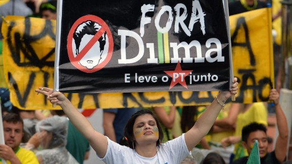 """A demonstrator holds a banner reading """"Dilma out and take the Workers' Party with you."""""""