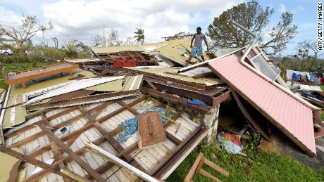 "In this photo taken on March 16, 2015 a man looks through the ruins of his home in Vanuatu's capital Port Villa after Cyclone Pam ripped through the island nation. The UN said on March 17, 2015 that twenty-four people have been killed by Cyclone Pam, as the Pacific nation's president pleaded for help to rebuild the archipelago's ""completely destroyed"" infrastructure. AFP PHOTO / POOL / DAVE HUNTDAVE HUNT/AFP/Getty Images"