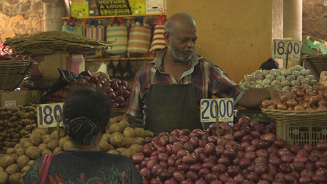 Market stalls sell local produce, catering to a variety of cultures that make up cuisine on the island.