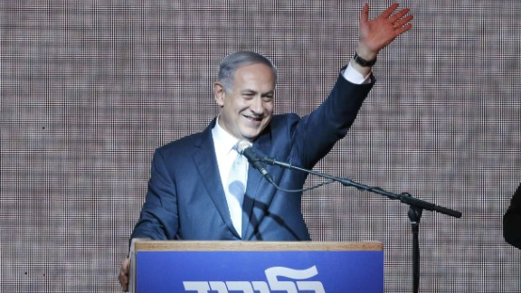 Israeli Prime Minister Benjamin Netanyahu waves from the stage as he reacts to exit poll figures in Israel