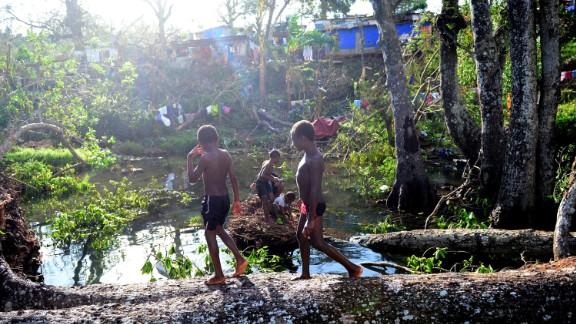 Children play on March 17 in water among fallen trees near Port Vila.