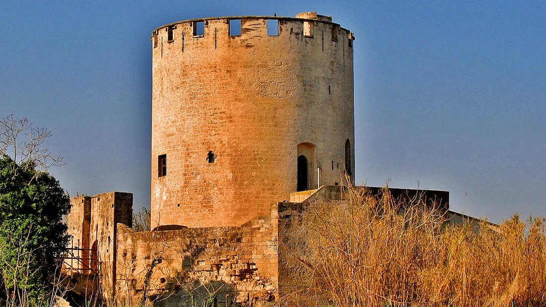 "A queen loved to bathe in waters surrounding this fortified structure, built by the Anjou dynasty in 1200.<br />The tower rises on a cliff in the middle of a deep pond. <br />Its name means ""beautiful place"" -- it was conceived as a Garden of Eden with lemon groves, figs, cherries, nuts and almond trees. <em><br />Viale San Nicola, Lecce</em>"