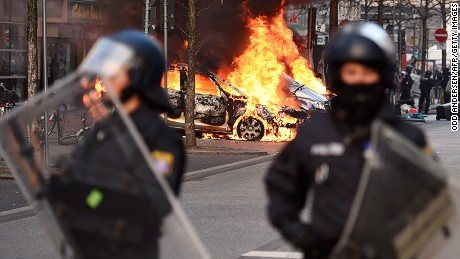 Riot Police form a cordon as a Police car burns on the opening day of the European Central Bank (ECB) in Frankfurt am Main, western Germany, on March 18, 2015.
