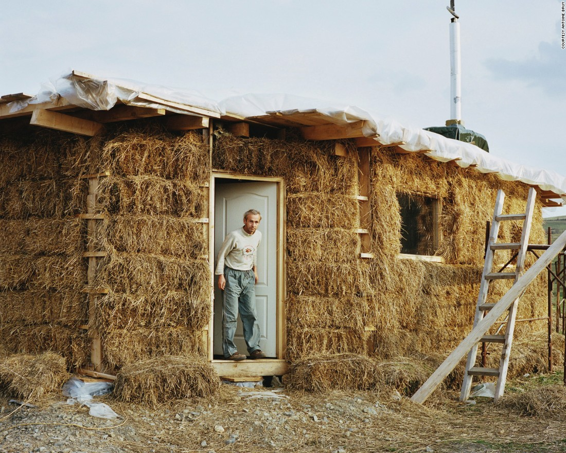 A man peers out from a house made of straw near the town of Zlatna in the Apuseni Mountains, Romania. <br /><br />Bruy visited five different countries -- France, Spain, Switzerland, Romania and Wales -- in carrying out his project.