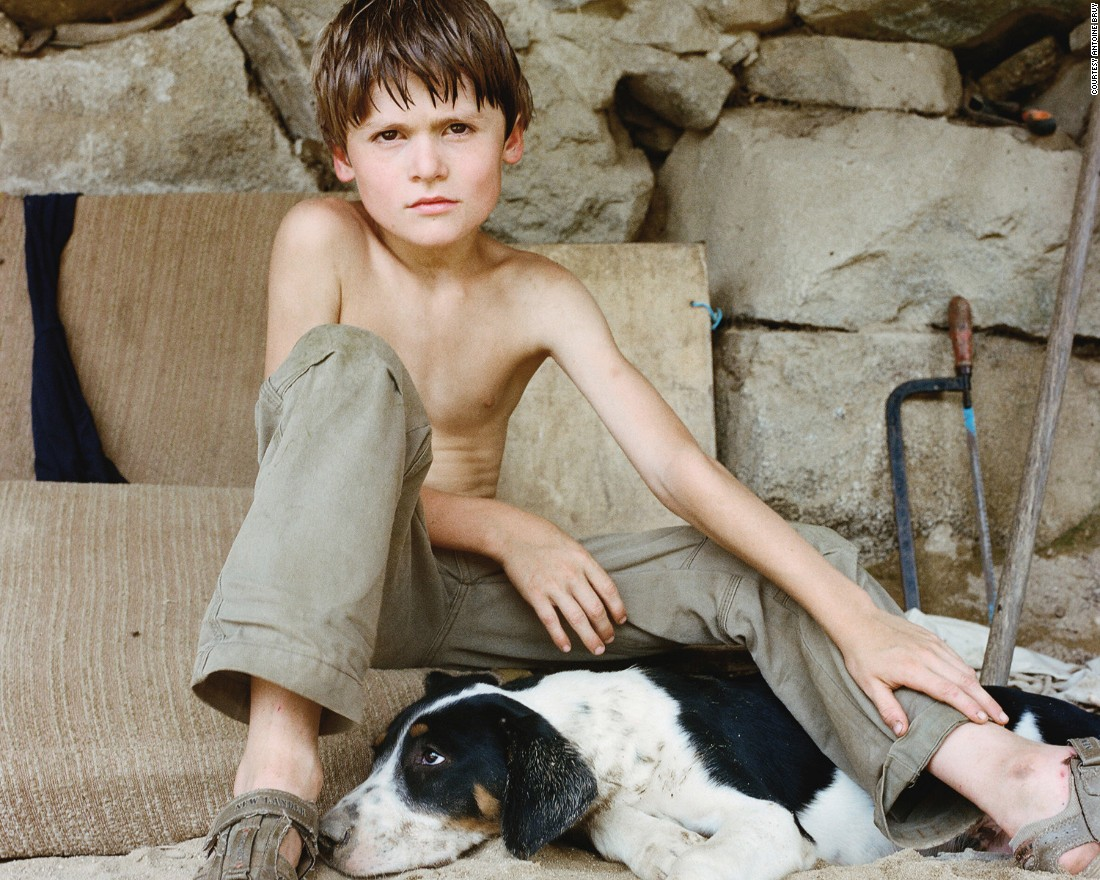 A boy gazes intensely at Bruy's lens while stroking his dog.<br /><br />