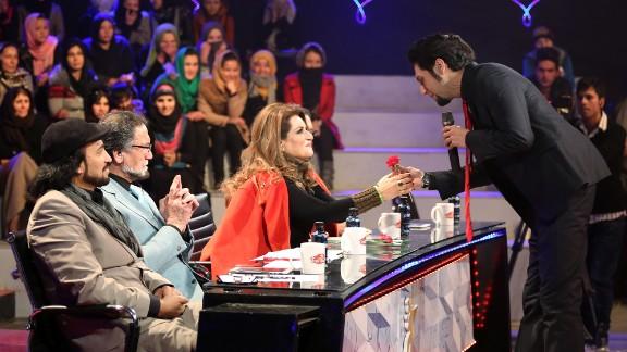 Singer Arash Barez gives a flower to a judge on International Women's Day.