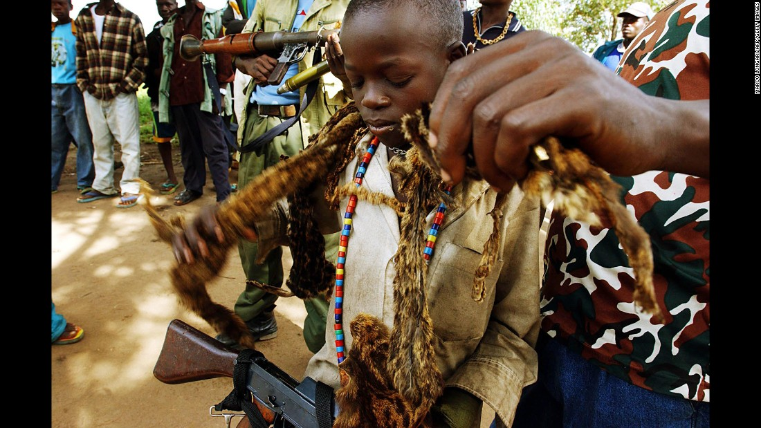 A child soldier is helped by another militiaman as he puts on the traditional chief's hyena skins in an undisclosed location near Bunia in the Democratic Republic of Congo in 2003.
