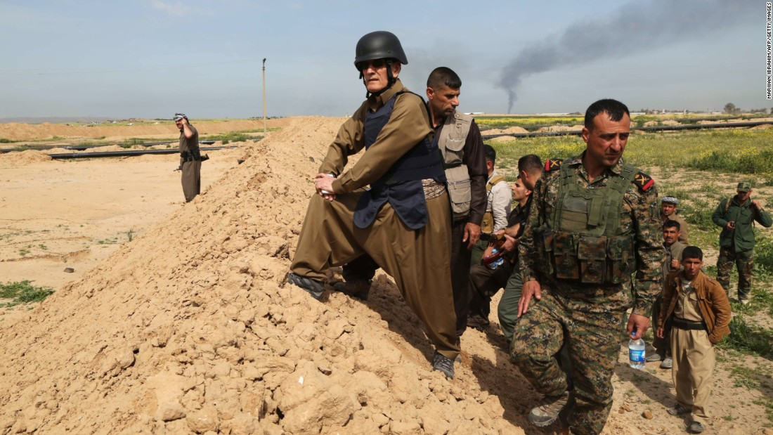 The Iraqi governor of Kirkuk, Najmiddin Karim stands on a trench alongside Iraqi Kurdish Peshmerga fighters in the city of Kirkuk in March 2015, after the Peshmerga fighters reportedly re-took parts of the area from ISIS.