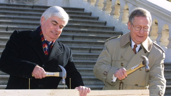 "Sen. Christopher Dodd, D-Connecticut, and McConnell hammer the ""first nails"" into a piece of wood during a nail-driving ceremony in December 2000 on Capitol Hill. Both senators participated in the ceremony to signify the beginning of construction of the 2001 Inaugural platform on the West Front Terrace of the U.S. Capitol."