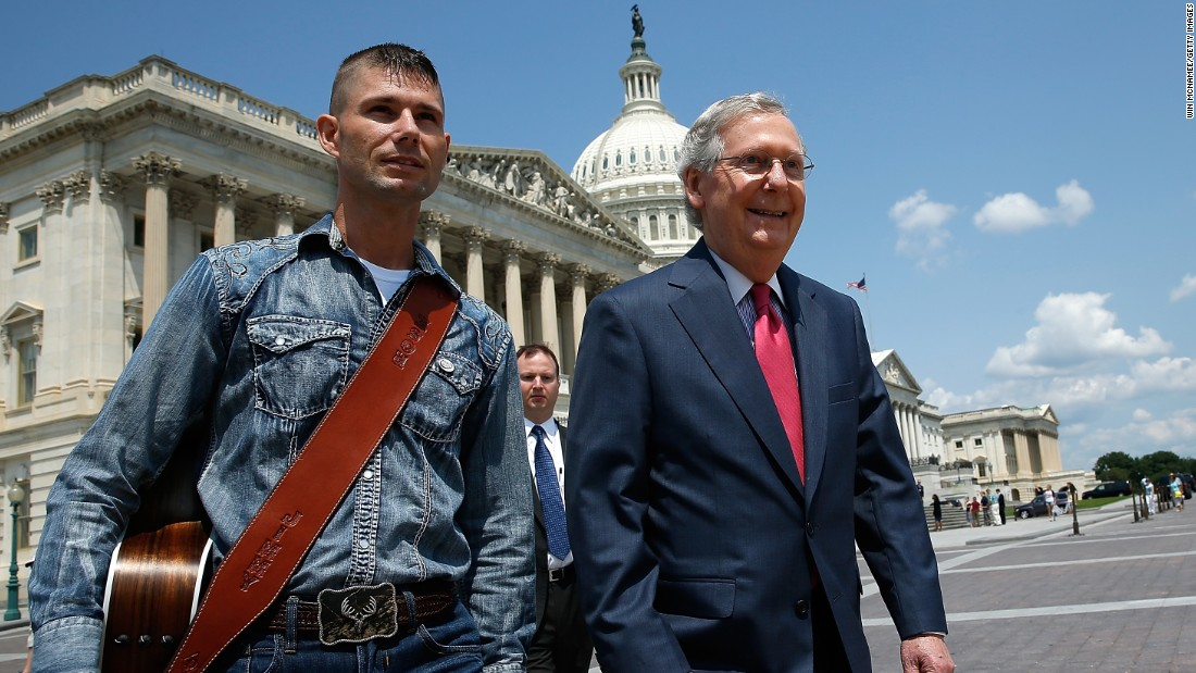 "McConnell walks with ""America's Got Talent"" contestant Jimmy Rose to a news conference on the economic ramifications of the Environmental Protection Agency's proposed power plant rules in July 2014."