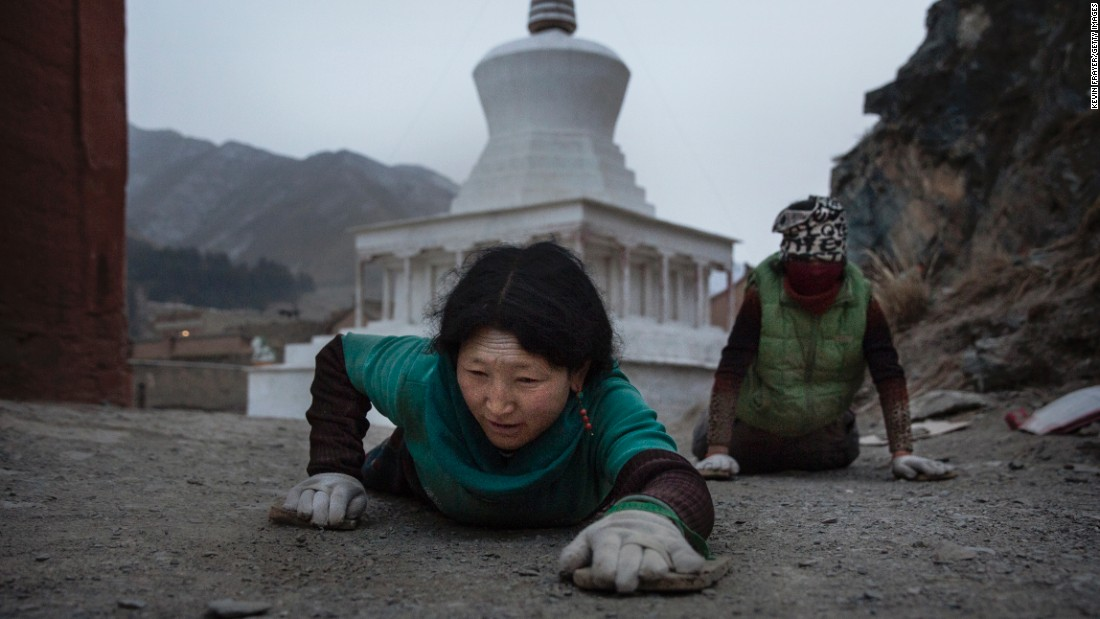 A Tibetan Buddhist prostrates herself on the ground during a pilgrimage for Monlam on March 3, 2015 at Labrang Monastery.