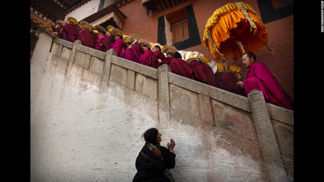 A woman prays as monks of the Yellow Hat order, carry a large thangka of Buddha after showing it to worshippers on March 3, 2015.