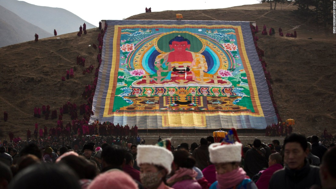 Monks unveil a large thangka -- a painting on silk or cotton -- showing Buddha, on a hillside near Labrang Monastery on March 3, 2015.