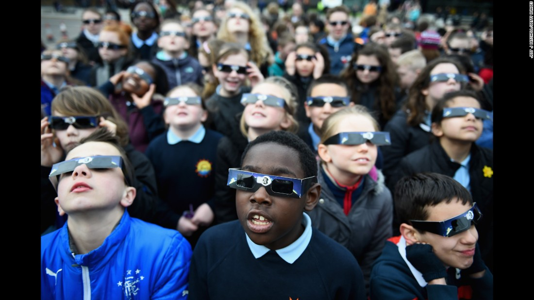 Schoolchildren look into the sky at a partial solar eclipse over Glasgow, Scotland.