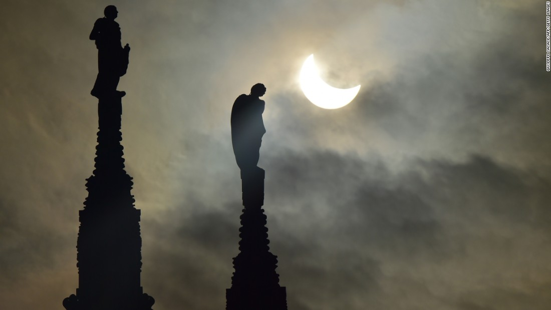 The partial solar eclipse is visible next to cathedral statues in Milan, Italy.