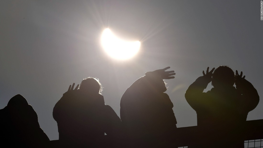People watch as the solar eclipse begins over Cornwall, England.