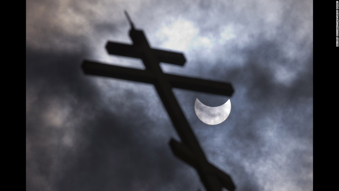 The partial solar eclipse is visible behind a cross on the Church of St. Nicholas in Sofia, Bulgaria.