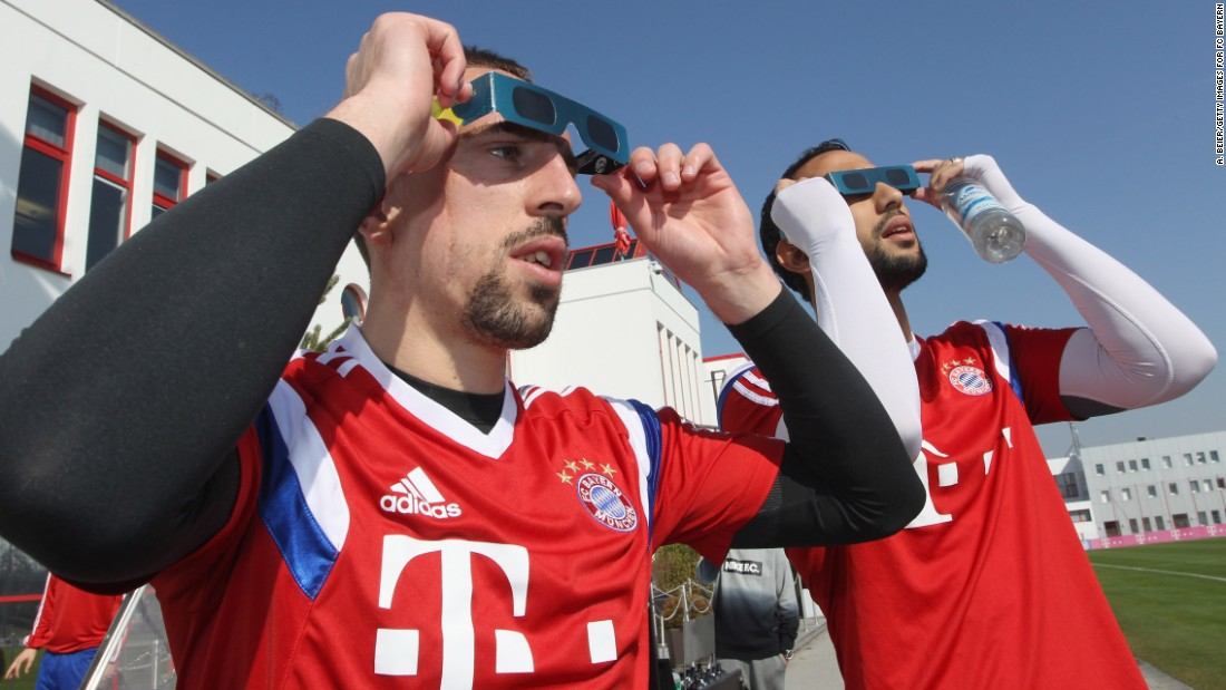 Franck Ribery, left, and Medhi Benatia of Bayern Muenchen soccer team watch the eclipse before a training session in Munich, Germany.
